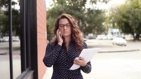 Junge schöne Geschäftsfrau, die in die Stadt mit Dokumenten geht und am Telefon spricht stock video