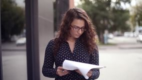 Junge schöne Geschäftsfrau geht durch die Stadtzeichendokumente stock footage