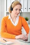 Junge schöne Geschäftsfrau im Kopfhörer oder im Anrufbetreiber steht durch Laptop-Computer in Verbindung Orange Strickjacke ist U Stockbild