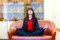 Junge schöne Geschäftsfrau meditiert auf Sofa im Büro Lizenzfreie Stockfotos