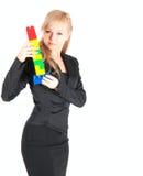 Junge schöne Geschäftsfrau mit Plastik blockt die Aufstellung auf weißem Hintergrund Lizenzfreies Stockfoto