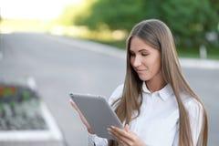 Junge schöne Geschäftsfraustudentengeschäftsfrau benutzt Tablette die im Freien lizenzfreie stockfotografie