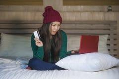 Junge schöne glückliche asiatische koreanische Frau im Winterhut entspannt auf Bettholdingkreditkarte unter Verwendung der Laptop stockfotografie