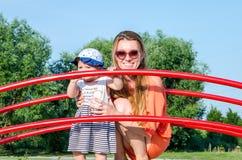 Junge schöne glückliche Familie des Mutter- und Tochterbabys, die auf dem Schwingen spielt, und Fahrt im Vergnügungsparklächeln Stockfotos