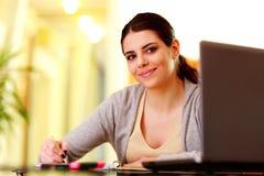 Junge schöne glückliche Frauenschreibensanmerkungen Lizenzfreies Stockfoto