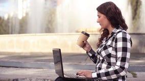 Junge schöne glückliche Geschäftsfrau, die an Laptop in der Stadt im Park arbeitet stock footage