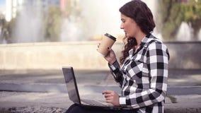 Junge schöne glückliche Geschäftsfrau, die an Laptop im Park nahe Brunnen arbeitet stock footage