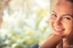 Junge schöne glückliche lächelnde gebräunte Frau, die sonnigen Tag des Kameraporträts mit Kopienraum während der tropischen Somme stockfotos