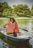 Junge schöne glückliche liebevolle Paare, die ein kleines Boot auf einem See rudern Ein Spaßdatum in der Natur Paare in einem Boo stockfotografie