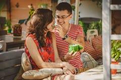 Junge schöne glückliche liebevolle Paare, die am Straßenfreiluftcafé sitzen Männer gibt seiner Freundin Bonbons Anfang von Liebe  lizenzfreie stockfotografie