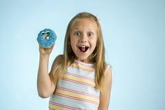 Junge schöne glückliche und aufgeregte blonde alte haltene Donut-Wüste des Mädchens 8 oder 9 Jahre auf ihrer Hand, die spastisch  Lizenzfreies Stockfoto