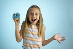Junge schöne glückliche und aufgeregte blonde alte haltene Donut-Wüste des Mädchens 8 oder 9 Jahre auf ihrer Hand, die spastisch  Lizenzfreie Stockfotos