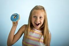 Junge schöne glückliche und aufgeregte blonde alte haltene Donut-Wüste des Mädchens 8 oder 9 Jahre auf ihrer Hand, die spastisch  Stockbild