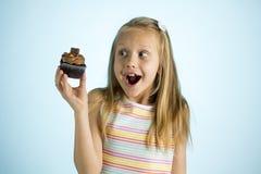 Junge schöne glückliche und aufgeregte blonde alte haltene Schokoladenkuchen des Mädchens 8 oder 9 Jahre auf ihrer Hand, die spas Lizenzfreie Stockfotos