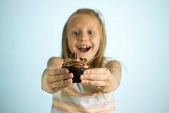 Junge schöne glückliche und aufgeregte blonde alte haltene Schokoladenkuchen des Mädchens 8 oder 9 Jahre auf ihrer Hand, die spas Stockfotografie