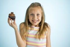 Junge schöne glückliche und aufgeregte blonde alte haltene Schokoladenkuchen des Mädchens 8 oder 9 Jahre auf ihrer Hand, die spas Lizenzfreie Stockfotografie