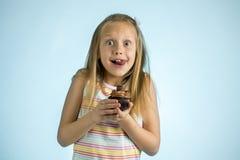 Junge schöne glückliche und aufgeregte blonde alte haltene Schokoladenkuchen des Mädchens 8 oder 9 Jahre auf ihrer Hand, die spas Stockfotos