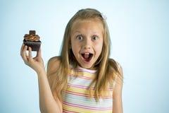 Junge schöne glückliche und aufgeregte blonde alte haltene Schokoladenkuchen des Mädchens 8 oder 9 Jahre auf ihrer Hand, die spas Lizenzfreie Stockbilder