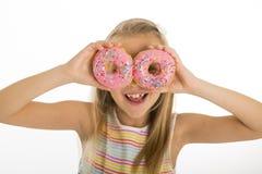 Junge schöne glückliche und aufgeregte blonde Schaumgummiringe der Holding zwei des Mädchens 8 oder 9 Jahre alte auf ihren Augen, Lizenzfreies Stockbild