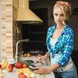Junge schöne Hausfrau kocht eine Mahlzeit des Frischgemüses in der Küche Lizenzfreies Stockfoto