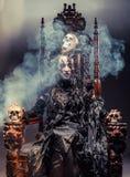 Junge schöne Hexe sitzt auf einem Stuhl Hell bilden Sie, Schädel, Rauchhalloween-Thema stockfotografie