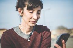 Junge schöne Hippie-Frau, die intelligentes Telefon verwendet Stockfoto