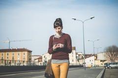 Junge schöne Hippie-Frau, die intelligentes Telefon verwendet Lizenzfreies Stockbild