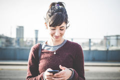 Junge schöne Hippie-Frau, die intelligentes Telefon verwendet Lizenzfreie Stockfotografie