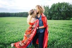 Junge schöne Hippiepaare, die auf dem grünen Sommergebiet gehen Lizenzfreie Stockbilder