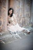 Junge schöne indische Frau, die draußen gegen Steinwand sitzt Stockfoto