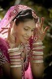 Junge schöne indische hindische Braut, die draußen im Garten sitzt Stockfoto