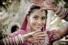 Junge schöne indische hindische Braut, die unter Baum mit den gemalten Händen angehoben steht Stockfotografie