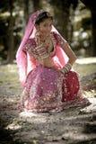 Junge schöne indische hindische Braut, die unter Baum sitzt Stockbild