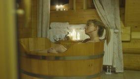 Junge schöne kaukasische Frau, die Bad in einer hölzernen Wanne nimmt Stockbild