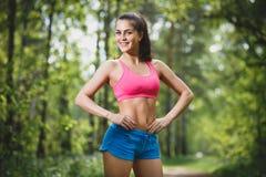 Junge schöne kaukasische Frau, die im Sommerpark rüttelt Lizenzfreies Stockfoto