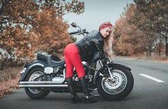 Junge schöne kaukasische Frau, die mit Motorrad aufwirft stockbild