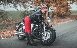 Junge schöne kaukasische Frau, die mit Motorrad aufwirft lizenzfreies stockbild