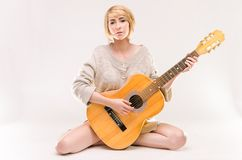 Junge schöne lächelnde blonde Dame in der grauen Strickjacke, die Akustikgitarre spielt Stockfotos