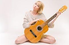 Junge schöne lächelnde blonde Dame in der grauen Strickjacke, die Akustikgitarre spielt Lizenzfreie Stockbilder