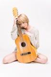 Junge schöne lächelnde blonde Dame in der grauen Strickjacke, die Akustikgitarre spielt Stockbilder