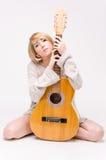Junge schöne lächelnde blonde Dame in der grauen Strickjacke, die Akustikgitarre spielt Stockfoto