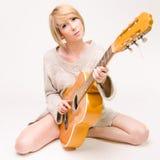 Junge schöne lächelnde blonde Dame in der grauen Strickjacke, die Akustikgitarre spielt Stockfotografie