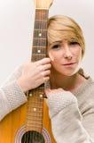 Junge schöne lächelnde blonde Dame in der grauen Strickjacke, die Akustikgitarre spielt Lizenzfreies Stockbild