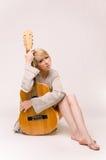 Junge schöne lächelnde blonde Dame in der grauen Strickjacke, die Akustikgitarre spielt Stockbild