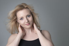Junge schöne lächelnde blonde Frau Stockfotografie
