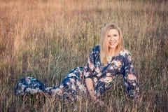 Junge schöne lächelnde Frau, die auf Gras im langen Abendkleid sitzt Lizenzfreies Stockbild