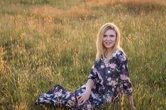 Junge schöne lächelnde Frau, die auf Gras im langen Kleid sitzt Lizenzfreie Stockfotos