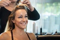 Junge schöne lächelnde Frau, die Haar gekräuselt erhält stockfotos