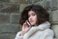 Junge schöne lächelnde Frau, die am Handy spricht Stockfotografie