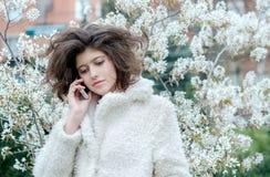 Junge schöne lächelnde Frau, die am Handy spricht Stockfoto